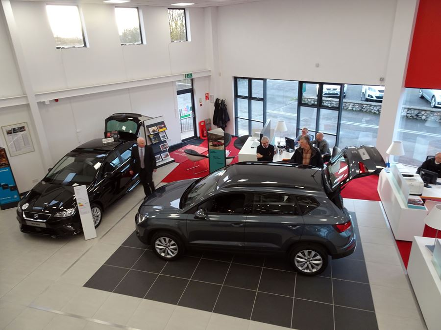 Looking down onto the dealership floor with cars, customers, and salespeople in fram