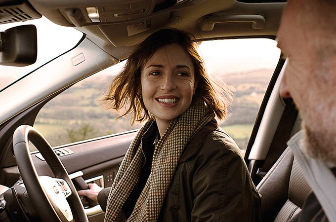 Smiling woman getting into driving seat of Land Rover